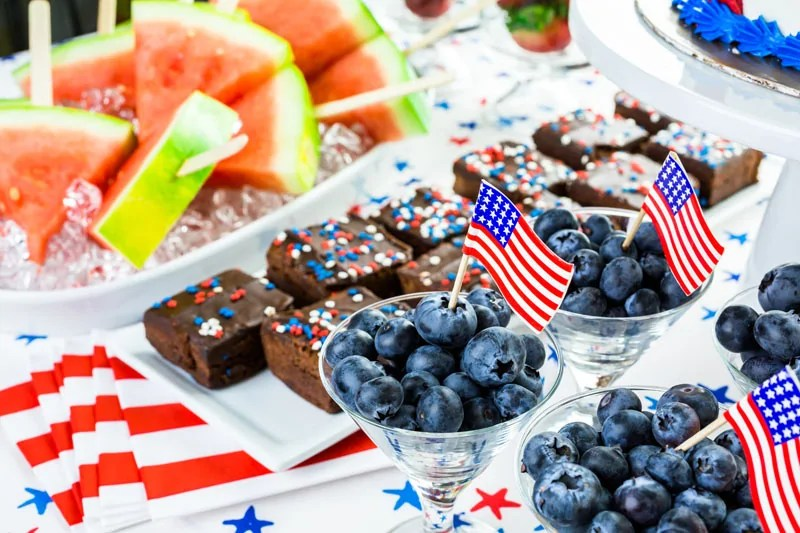 4th of July dessert table, with watermelon wedges on sticks, brownies with sprinkles, and glasses of blueberries topped with the US flag.