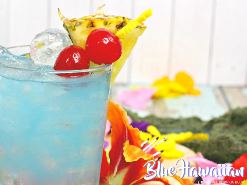 A glass of blue hawaiian cocktail garnished with cherries and pineapple, surrounded by tropical flowers