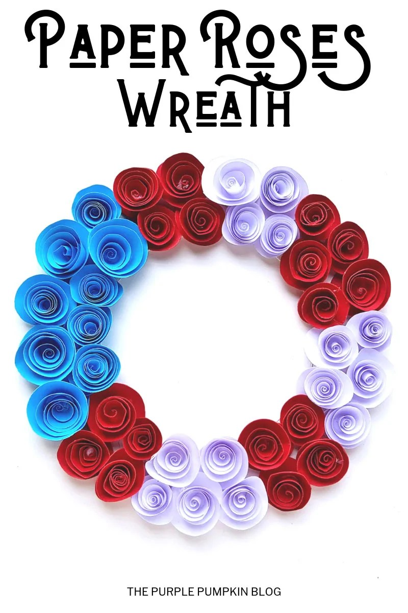 A homemade patriotic wreath, with red, white, and blue paper flowers on a white background.