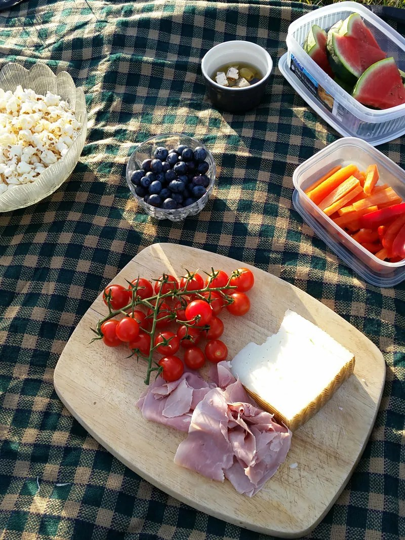 Green checkered picnic blanked with containers of picnic foods including watermelon, carrots, blueberries, popcorn, and olives. As well as a wooden board with on the vine tomatoes, ham, and manchego cheese.