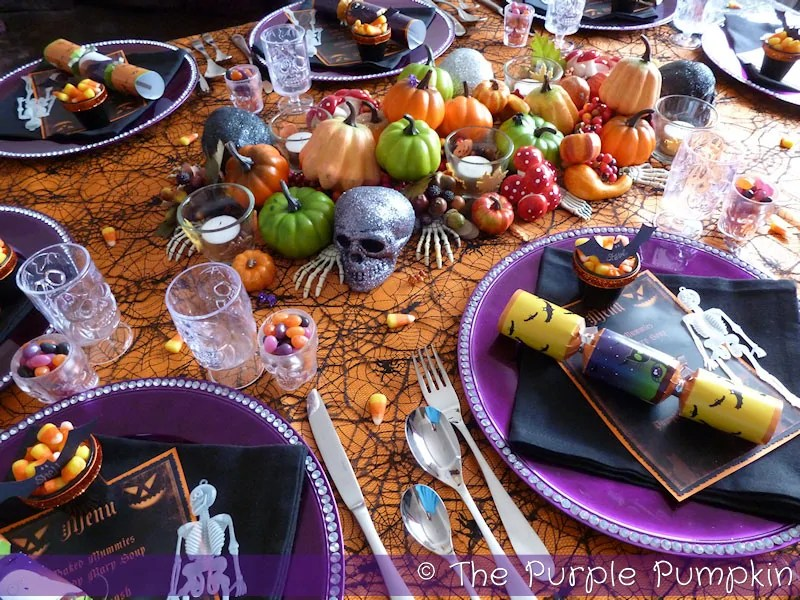 Halloween tablescape with purple plates, orange table cloth, and pumpkin and skull decorations