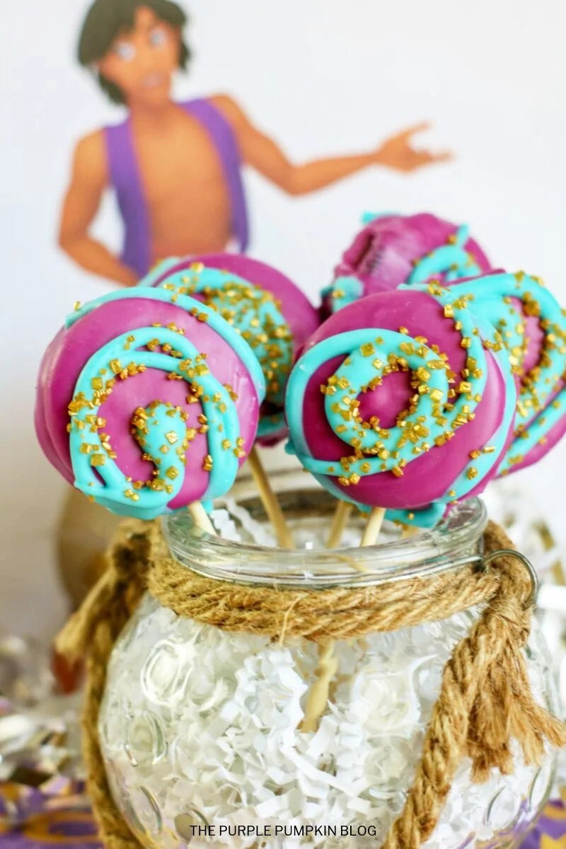 Oreos covered in purple candy melts, and swirled with blue candy and covered in gold sprinkles, on sticks in a jar.