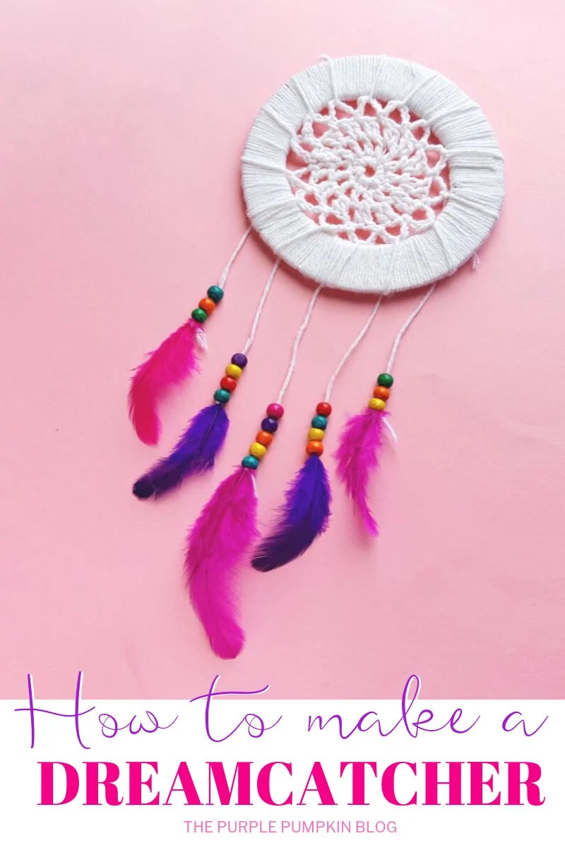 A homemade dreamcatcher on a pink background