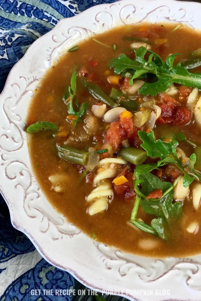 A bowl of minestrone soup with arugula
