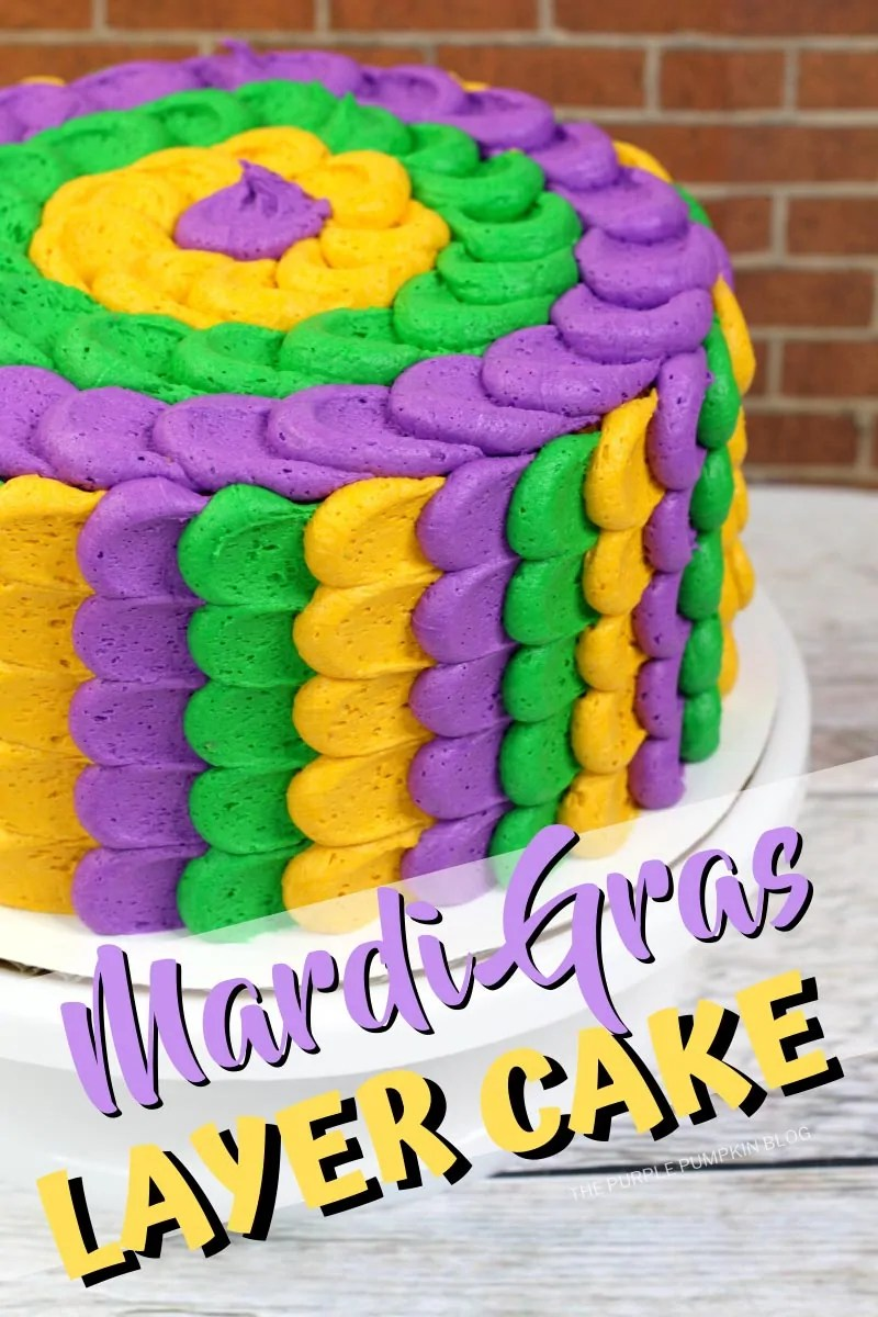 Mardi Gras Layer Cake sat upon a cake stand. Purple, Gold, and green frosting is piped around the sides and top in a scallop design.
