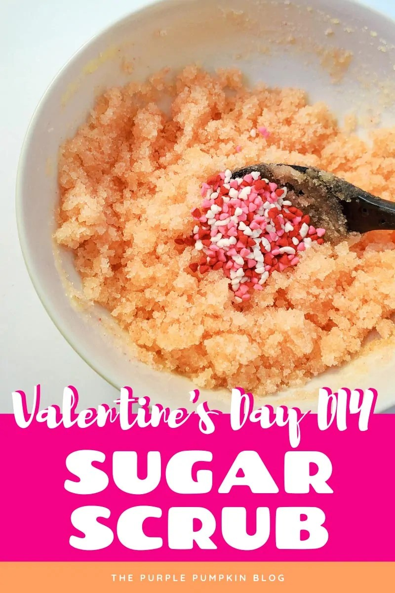 Valentine's Day DIY Sugar Scrub. A bowl of sugar scrub with a pile of heart-shaped sprinkles being mixed in with a spoon.