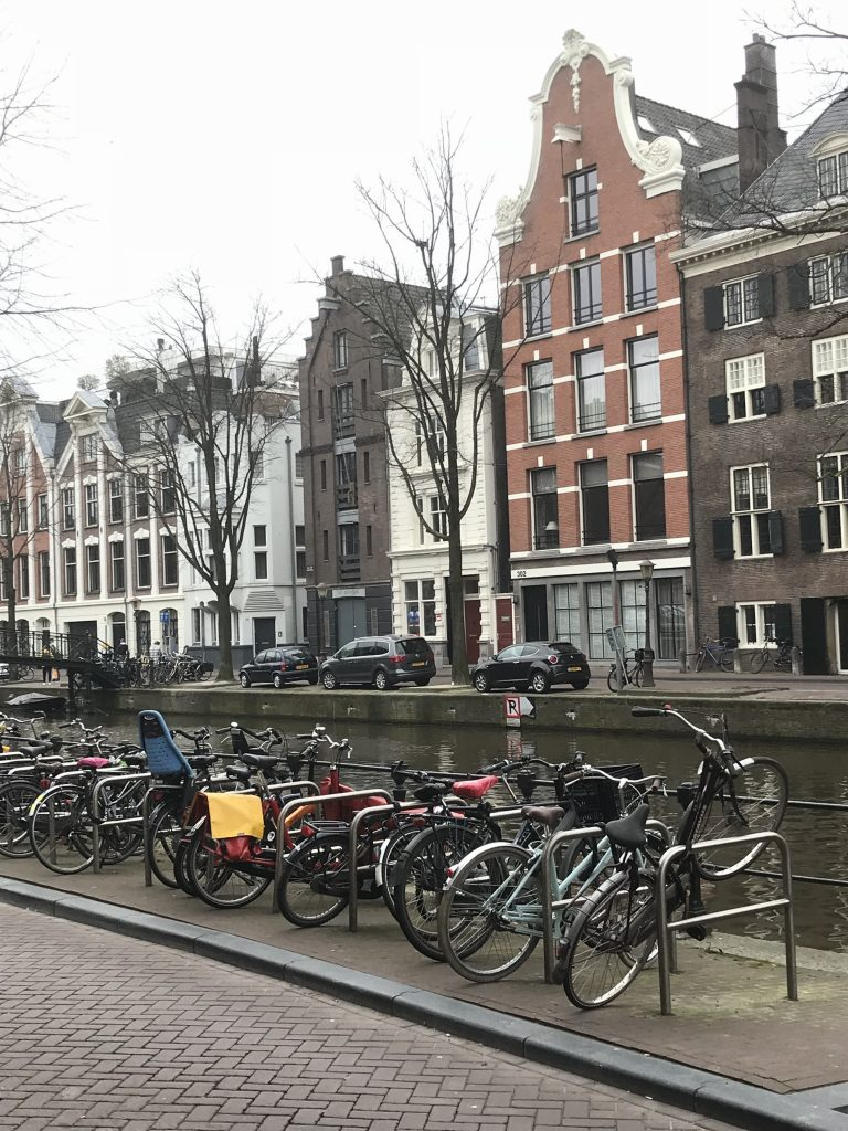 "This photo is a perfect synopsis of Amsterdam. The beautiful 3 and 4 story architecture, the canal and bikes pretty much sum up most of what Amsterdam is made up of..... the only thing really missing are the beautiful flowers, the Red Light District and the ""Coffee Houses!"