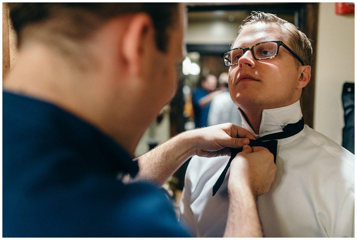Groomsmen tying grooms tie