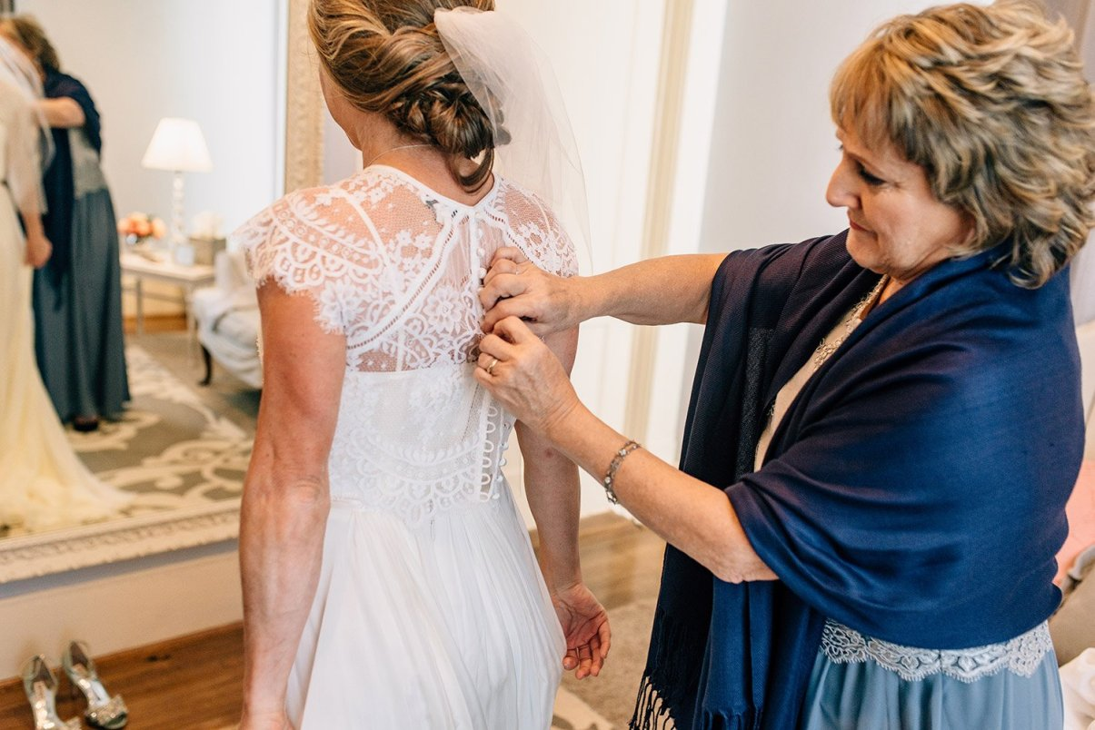 mother helps bride button dress