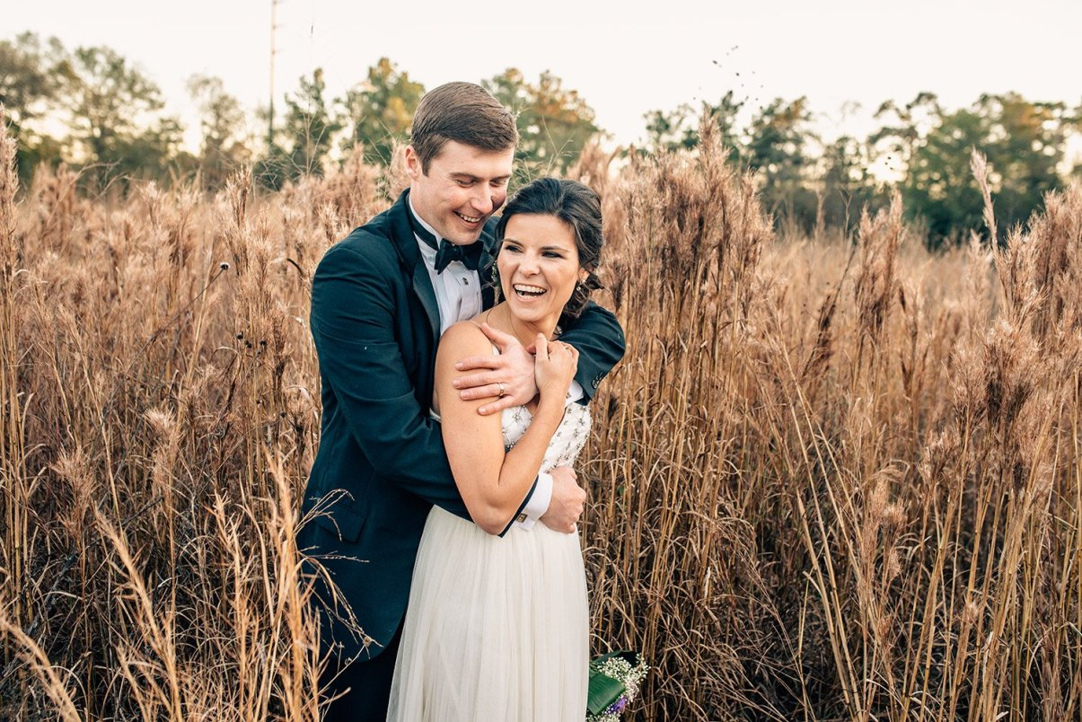 bride and groom laughing in field