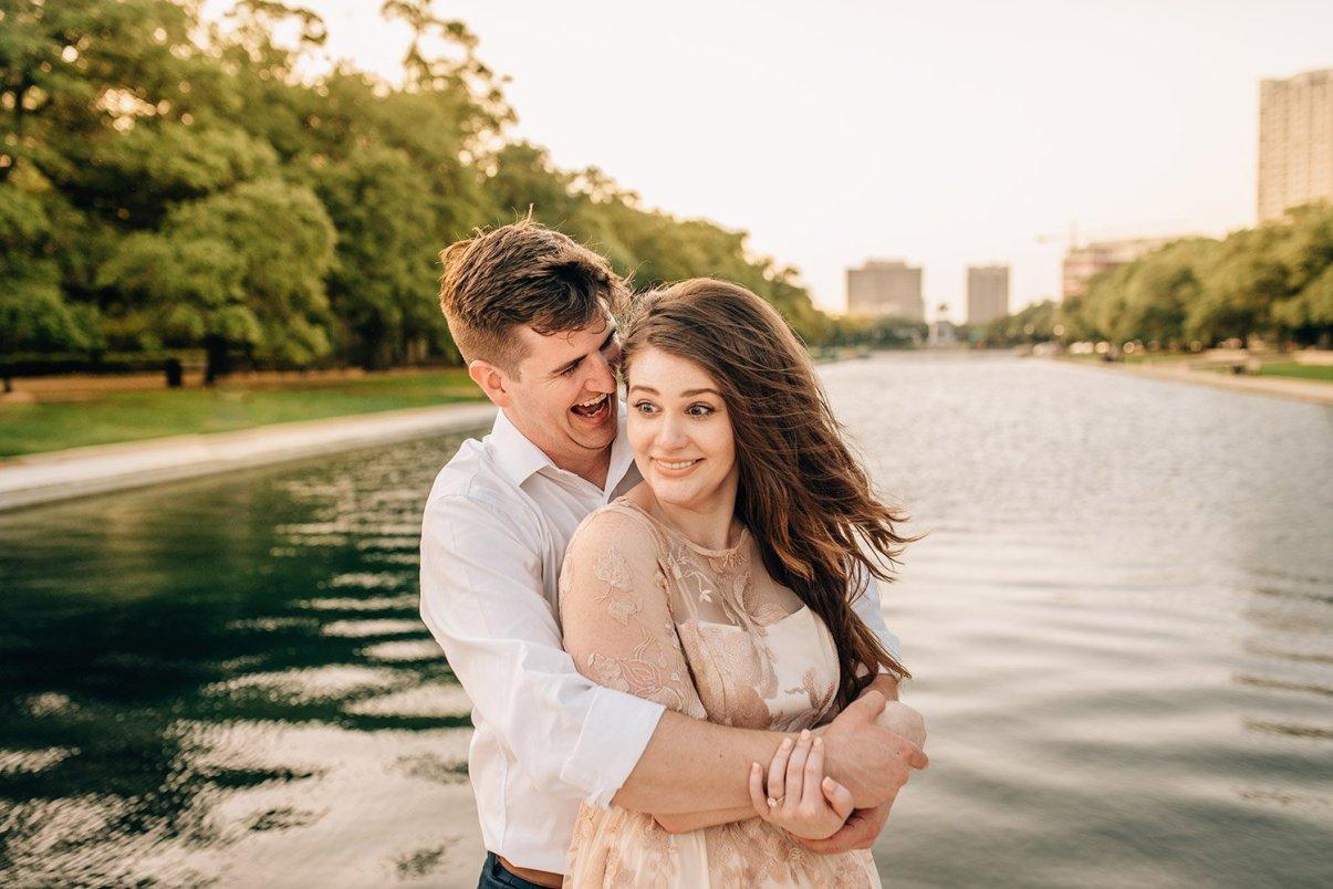 man whispering in fiancee's ear