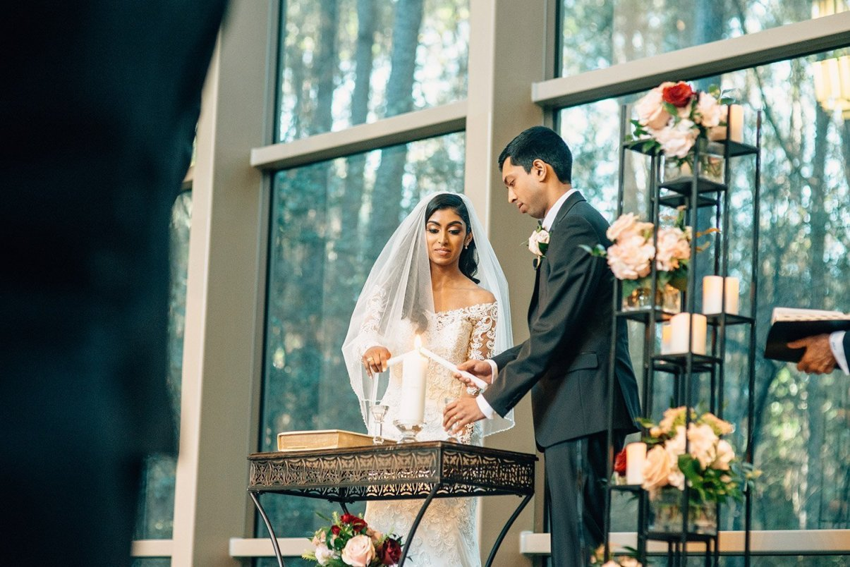 bride and groom lighting the unity candle at chapel in the woods