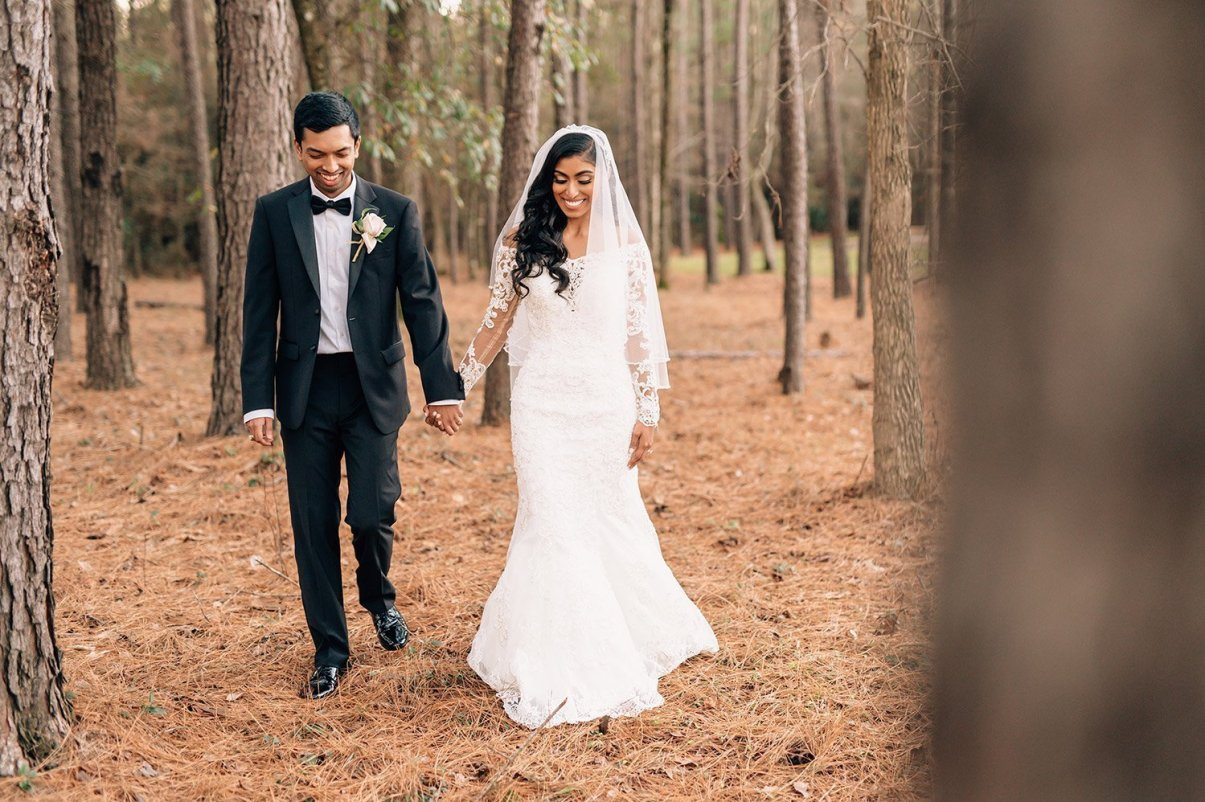 married couple walking through woods holding hands