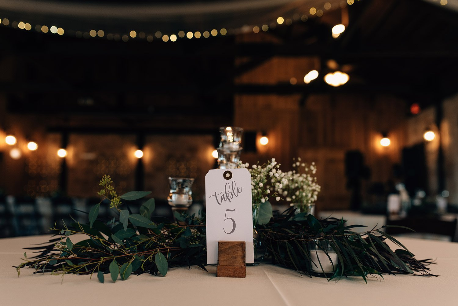 dark green table details on white table cloth and table numberer a wedding at the springs event center