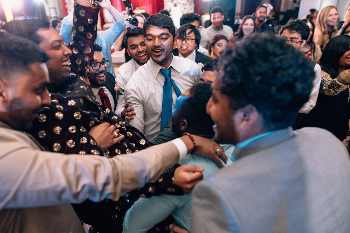 wedding guests lift groom during reception