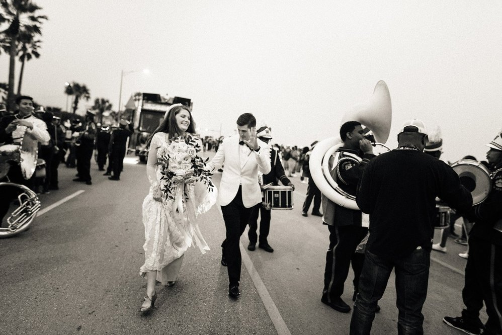 bride and groom outside with the galveston mardi gras parade