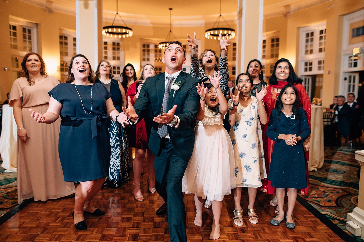groomsmen catches bouquet in Hotel Galvez Ballroom