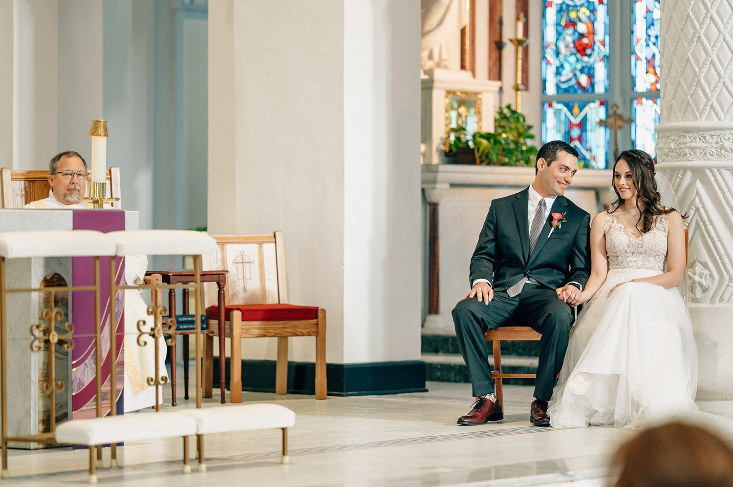bride and groom laugh together during wedding homily