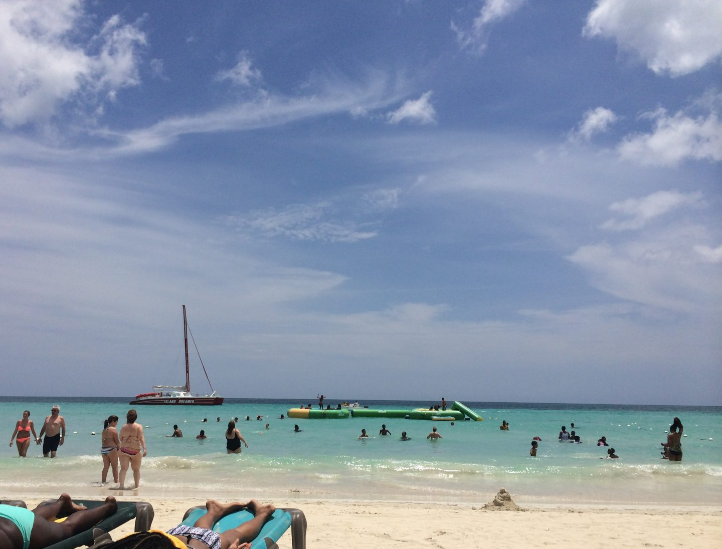 People sunbathing and water inflatables, swimmers and a boat in the water at 7 Mile Beach