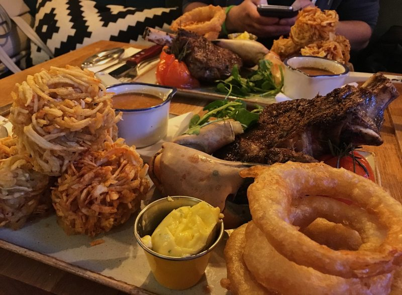 18oz ribeye, crab claw, homemade beer-battered onion rings, grilled tomato, Perl Las sauce and Covent Garden spiralized potatoes