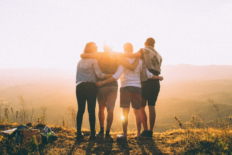 Group travel - four friends with their arms around each other , photographed from behind