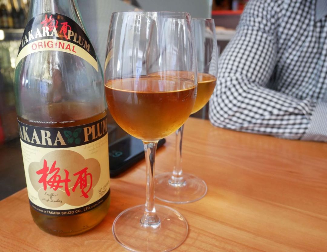 Takara Japanese plum wine bottle, with wine poured into glasses