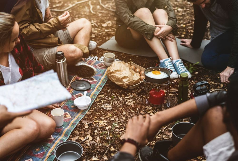 Group getaway: friends sat around a camping stove