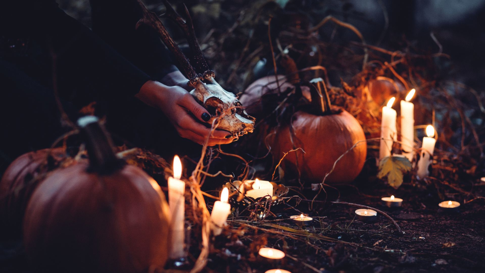 person decorating pumpkin and candles