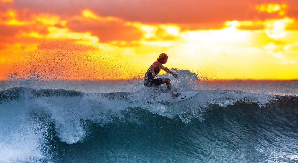man riding wave on surf board in front of sunset