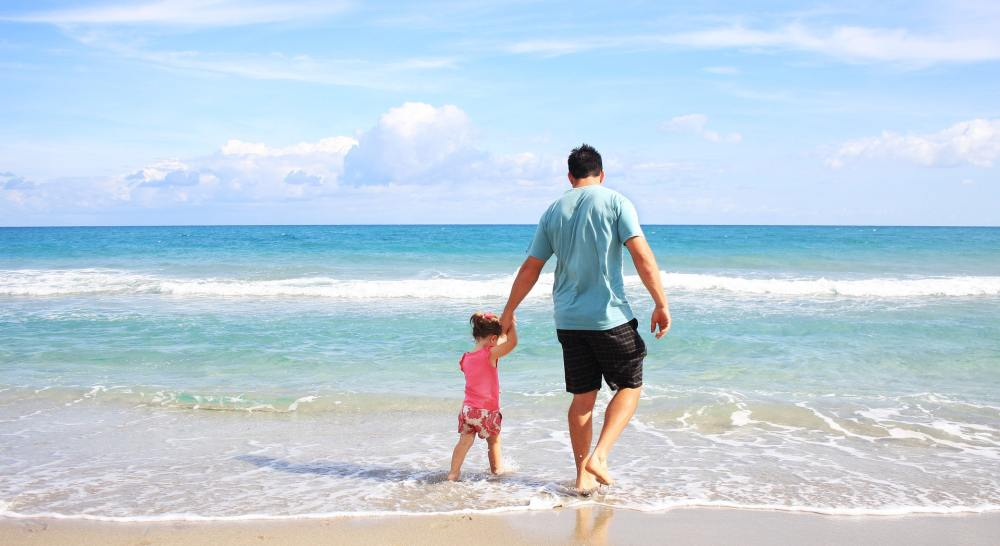 Man holding hand of child whilst they walk across the shore of the beach