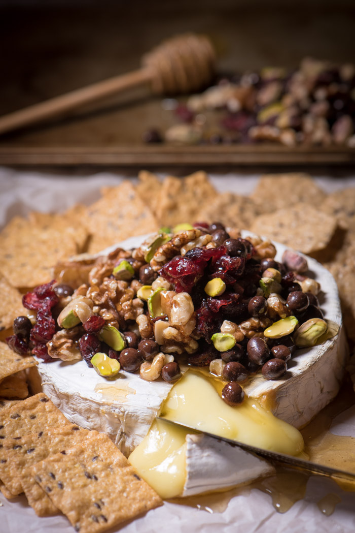 Baked Brie is one of the easiest last-minute appetizers I can think of! Top with nuts and dried fruit, drizzle honey and Enjoy! | The Recipe Wench