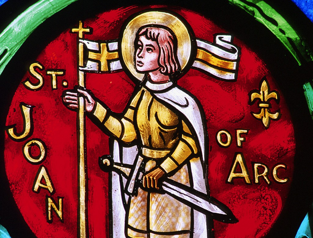 A church window depicts St. Joan of Arc with a sword. The French peasant girl was inspired by a series of saintly visions to help save France from the English in the Hundred Years' War. She led the victory at the besieged city of Orleans, but was later captured and burned at the stake. She is patron of France. Her feast is May 30. PHOTO: CNS/Crosiers