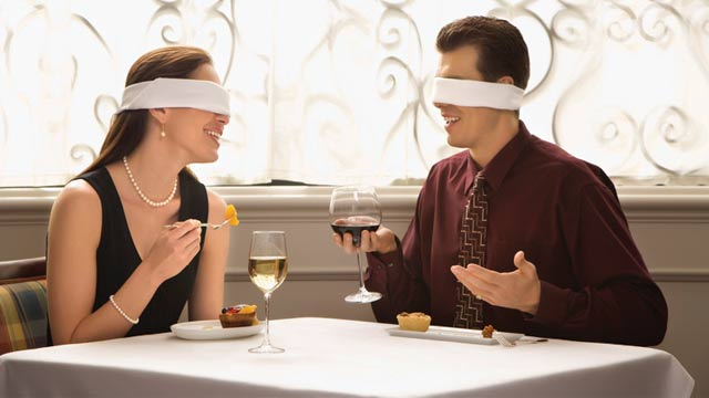 Couple dining with blindfolders on symbolizing how you can learn about people from their Mayan Astrology report.