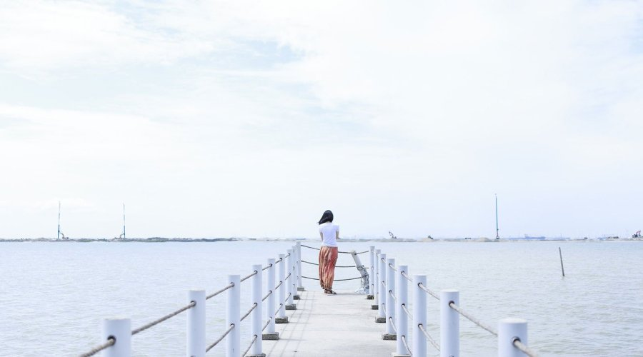 woman standing at the end of a pier