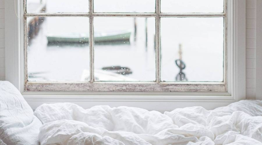 white linens on bed overlooking a boat floating in water
