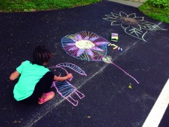 Girl drawing on pavement with chalk.