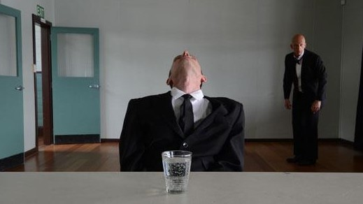 Man sitting at table with head thrown back