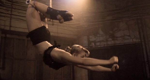 Trapeze artist Ellie Dubois swinging on trapeze using her legs