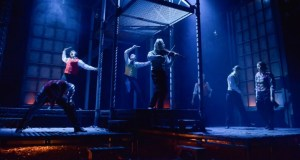 The cast are silhouetted against a set of iron girders bathed in blue light