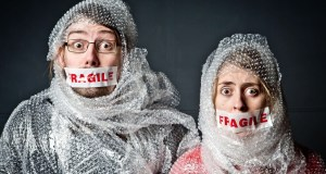 A male and female with Fragile Tape over their mouths and wrapped in Bubble Wrap