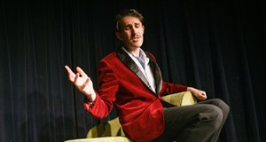 A man sits in a chair in a smoking jacket
