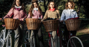 four women on wicker basketed bikes in edwardian dress