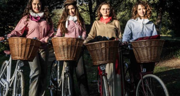 four women on wicker basketed bikes in edwardian dress