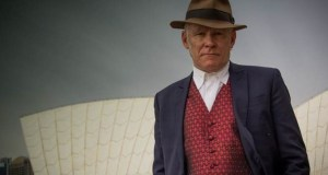 man in jacket waistcoat and hat stares at camera