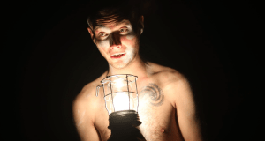 bare chested man holding storm light