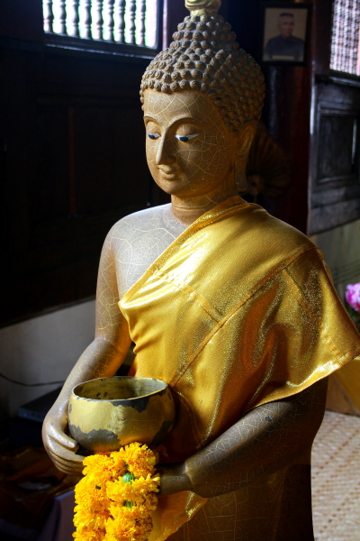 Buddha statue holding an alms bowl in Wat Pan Tao in Chiang Mai, Thailand