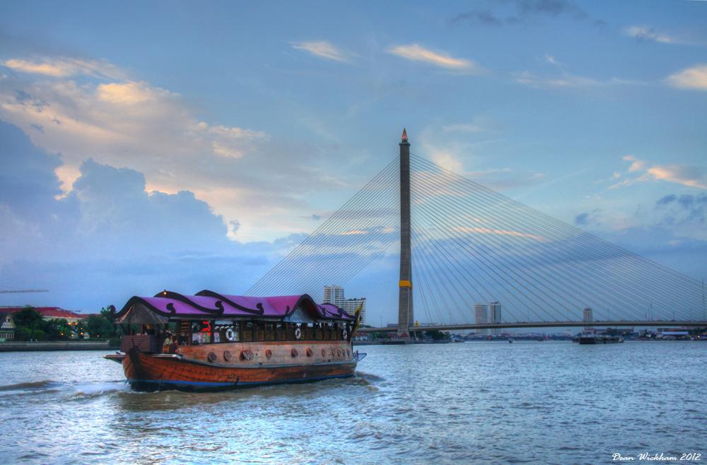 A wooden cruise boat at Rama VIII Bridge on the Chao Phraya River in Bangkok, Thailand
