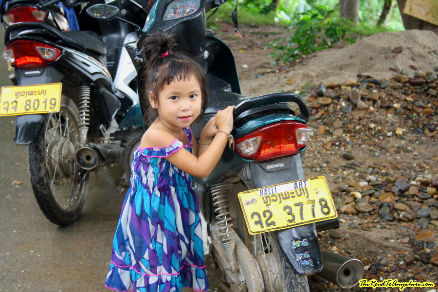 A little girl next to a motorbike in Luang Prabang, Laos