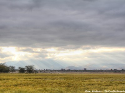 Rays of sunlight shine down on the grasslands near a Masai Village in Tanzania