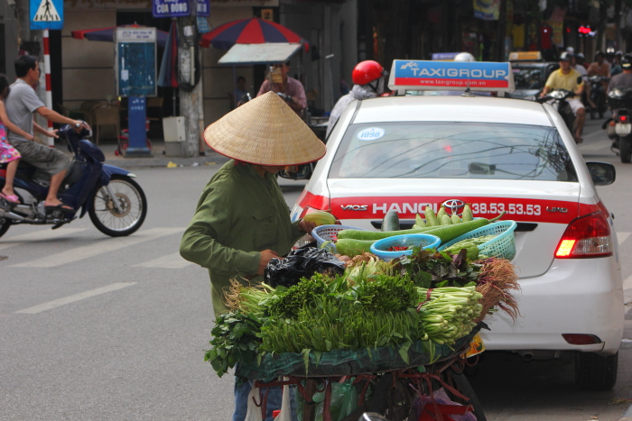 A man selling vegetables on his bicycle in Hanoi Vietnam
